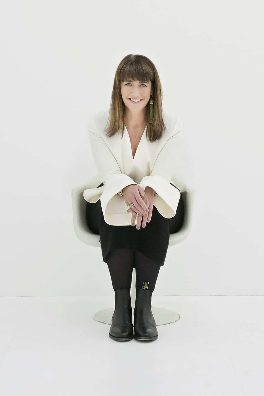 Megan Morton smiling, sitting on a chair
