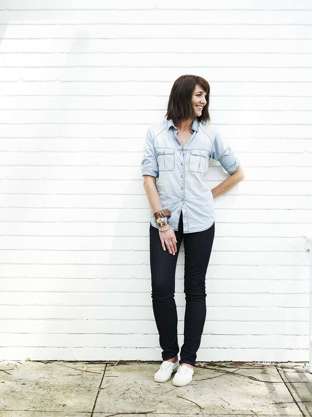 Megan Morton looking sideways and smiling, standing in front of a white brick wall